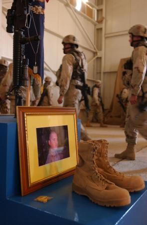 Soldiers from Company D, 2nd Battalion, 7th Infantry, 3rd Infantry Division, Task Force Liberty, file past the memorial of Pfc. Wesley R. Riggs. Their fallen comrade was killed in action May 17, 2005 in an improvised explosive attack in Mukasheefah, Iraq.