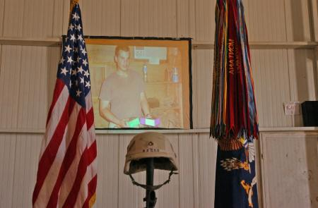 In honor of their fallen comrade, Soldiers of Company D, 2nd Battalion, 7th Infantry, 3rd Infantry Divisiion, Task Force Liberty, played a slide show of Pfc. Wesley R. Riggs before and after the memorial ceremony. Riggs was killed in action in an improvised explosive attack in Mukasheefah, Iraq, May 17, 2005.
