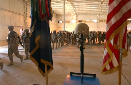 Soldiers from Company D, 2nd Battalion, 7th Infantry, 3rd Infantry Division, Task Force Liberty, file past a memorial of Pfc. Wesley R. Riggs. Their fallen comrade was killed in action May 17, 2005 in an improvised explosive attack in Mukasheefah, Iraq.