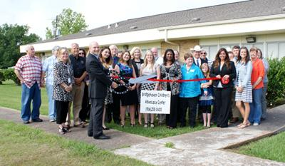 "County Attorney & Board President Scott Peal ""cuts"" the ribbon to announce the official opening of Bridgehaven Children's Advocacy Center satellite office located at the First United Baptist Church in Anahuac. Joining Peal are: front row (left to right); Executive Director Paula Barron, Staff members Adrienne Linscomb, Meagan Mitchell, Liz Pruitt, Ann Rogers, Jeneca Rogers, Program Director Rachel Caudill, Chamber of Commerce board member Donna Foster, President Robbie King. Back row (left to right) County Clerk Heather Hawthorne. Sheriff Deputy, Sherry Rundzieher, Pastor Gary Hillyard, DA Cheryl Lieck, County Judge Jimmy Sylvia, Commissioner Pct. 4 Rusty Senac, Sheriff Brian Hawthorne, along with (not in any order), Liberty DA & Board Director Logan Pickett, Board member Allen Conner, Special Investigator Liberty County Ivan Pieree, Asst. DA Eric Carcerano, Charlie Henry, West Chamber of Commerce President Missy Malachek, Asst. DA Kathy Esquievel and Alissa Beard."