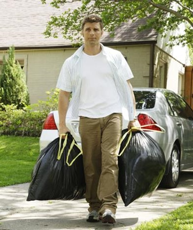 man_carrying_garbage_bags_on_drive_42-17005190
